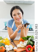 Купить «Smiling woman text messaging in front of vegetables in kitchen», фото № 30029983, снято 29 августа 2013 г. (c) Wavebreak Media / Фотобанк Лори
