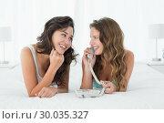 Купить «Relaxed young female friends using phone in bed», фото № 30035327, снято 14 августа 2013 г. (c) Wavebreak Media / Фотобанк Лори