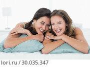 Купить «Smiling young female friends lying in bed», фото № 30035347, снято 14 августа 2013 г. (c) Wavebreak Media / Фотобанк Лори