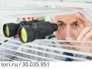 Mature businessman peeking with binoculars through blinds. Стоковое фото, агентство Wavebreak Media / Фотобанк Лори