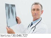 Купить «Confident doctor with xray picture of lungs», фото № 30046727, снято 4 октября 2013 г. (c) Wavebreak Media / Фотобанк Лори