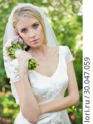 Купить «Pretty bride holding her bouquet wearing a veil», фото № 30047059, снято 9 октября 2013 г. (c) Wavebreak Media / Фотобанк Лори