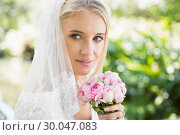 Купить «Smiling bride wearing veil holding bouquet», фото № 30047083, снято 9 октября 2013 г. (c) Wavebreak Media / Фотобанк Лори
