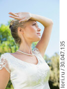 Купить «Pretty blonde bride holding arm to forehead on sunny day», фото № 30047135, снято 9 октября 2013 г. (c) Wavebreak Media / Фотобанк Лори