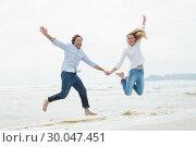 Купить «Cheerful couple holding hands and jumping at beach», фото № 30047451, снято 10 октября 2013 г. (c) Wavebreak Media / Фотобанк Лори