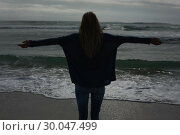 Купить «Silhouette rear view of woman with arms outstretched at beach», фото № 30047499, снято 10 октября 2013 г. (c) Wavebreak Media / Фотобанк Лори