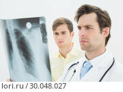 Купить «Concentrated doctor and patient examining lungs xray», фото № 30048027, снято 2 октября 2013 г. (c) Wavebreak Media / Фотобанк Лори
