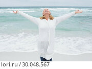 Купить «Senior woman with arms outstretched at beach», фото № 30048567, снято 11 октября 2013 г. (c) Wavebreak Media / Фотобанк Лори