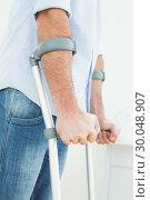 Купить «Closeup mid section of a young man with crutches», фото № 30048907, снято 16 октября 2013 г. (c) Wavebreak Media / Фотобанк Лори