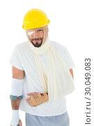 Купить «Man in hard hat with broken hand and crutch», фото № 30049083, снято 16 октября 2013 г. (c) Wavebreak Media / Фотобанк Лори