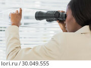 Купить «Businesswoman peeking with binoculars through blinds», фото № 30049555, снято 3 ноября 2013 г. (c) Wavebreak Media / Фотобанк Лори