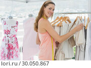 Купить «Beautiful female fashion designer with rack of clothes», фото № 30050867, снято 5 ноября 2013 г. (c) Wavebreak Media / Фотобанк Лори