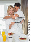 Young couple reading newspaper while having breakfast at home. Стоковое фото, агентство Wavebreak Media / Фотобанк Лори