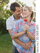 Young couple holding a flower in the park. Стоковое фото, агентство Wavebreak Media / Фотобанк Лори