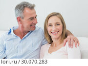 Купить «Relaxed couple sitting on sofa with arm around», фото № 30070283, снято 18 октября 2013 г. (c) Wavebreak Media / Фотобанк Лори