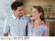 Купить «Couple with arm around at bakery», фото № 30072807, снято 11 декабря 2013 г. (c) Wavebreak Media / Фотобанк Лори