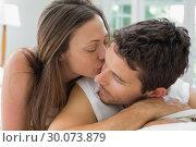 Купить «Young woman kissing man in bed», фото № 30073879, снято 12 декабря 2013 г. (c) Wavebreak Media / Фотобанк Лори