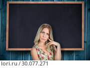 Купить «Composite image of frowning pretty blonde wearing flowered dress posing», фото № 30077271, снято 25 марта 2014 г. (c) Wavebreak Media / Фотобанк Лори