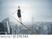 Купить «Composite image of businesswoman doing a balancing act», фото № 30078543, снято 28 марта 2014 г. (c) Wavebreak Media / Фотобанк Лори