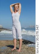 Купить «Blonde woman standing on rock stretching arms», фото № 30078947, снято 14 февраля 2014 г. (c) Wavebreak Media / Фотобанк Лори