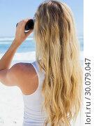 Купить «Blonde looking to the ocean through binoculars», фото № 30079047, снято 14 февраля 2014 г. (c) Wavebreak Media / Фотобанк Лори