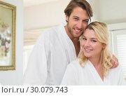 Купить «Cute couple in bathrobes smiling at camera together», фото № 30079743, снято 24 января 2014 г. (c) Wavebreak Media / Фотобанк Лори