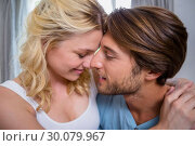 Cute young couple relaxing on bed together. Стоковое фото, агентство Wavebreak Media / Фотобанк Лори