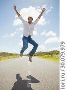 Купить «Handsome casual man leaping on a road smiling at camera», фото № 30079979, снято 24 января 2014 г. (c) Wavebreak Media / Фотобанк Лори