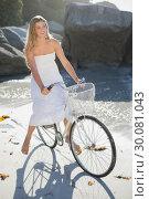 Beautiful blonde in white sundress on bike ride at the beach. Стоковое фото, агентство Wavebreak Media / Фотобанк Лори