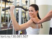 Купить «Fit brunette using weights machine for arms with trainer touching shoulders», фото № 30081507, снято 26 февраля 2014 г. (c) Wavebreak Media / Фотобанк Лори