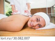 Купить «Smiling woman getting a back massage with herbal compresses», фото № 30082007, снято 9 апреля 2014 г. (c) Wavebreak Media / Фотобанк Лори