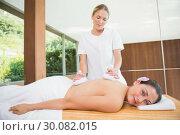 Купить «Smiling woman getting a back massage with herbal compresses», фото № 30082015, снято 9 апреля 2014 г. (c) Wavebreak Media / Фотобанк Лори
