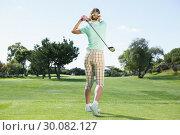 Купить «Female golfer taking a shot», фото № 30082127, снято 3 апреля 2014 г. (c) Wavebreak Media / Фотобанк Лори