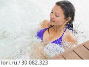 Купить «Smiling brunette in bikini relaxing in hot tub», фото № 30082323, снято 8 апреля 2014 г. (c) Wavebreak Media / Фотобанк Лори