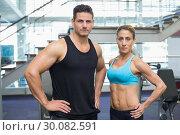 Купить «Bodybuilding man and woman frowning at camera», фото № 30082591, снято 2 апреля 2014 г. (c) Wavebreak Media / Фотобанк Лори