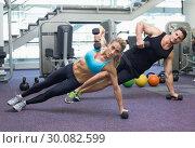 Купить «Bodybuilding man and woman holding dumbbells in plank position», фото № 30082599, снято 2 апреля 2014 г. (c) Wavebreak Media / Фотобанк Лори