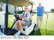 Happy golfing couple setting out for the day on buggy. Стоковое фото, агентство Wavebreak Media / Фотобанк Лори