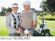 Купить «Happy golfing couple with golf buggy behind», фото № 30082943, снято 3 апреля 2014 г. (c) Wavebreak Media / Фотобанк Лори