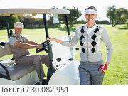 Купить «Happy golfing couple smiling at camera with their buggy», фото № 30082951, снято 3 апреля 2014 г. (c) Wavebreak Media / Фотобанк Лори