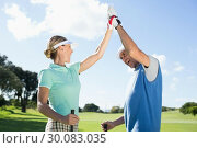 Купить «Golfing couple high fiving on the golf course», фото № 30083035, снято 3 апреля 2014 г. (c) Wavebreak Media / Фотобанк Лори