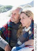 Купить «Happy couple wrapped up in blanket sitting on the beach», фото № 30083227, снято 3 апреля 2014 г. (c) Wavebreak Media / Фотобанк Лори
