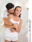 Attractive couple hugging in their pajamas. Стоковое фото, агентство Wavebreak Media / Фотобанк Лори
