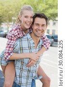 Купить «Young hip man giving his blonde girlfriend a piggy back», фото № 30084235, снято 19 февраля 2014 г. (c) Wavebreak Media / Фотобанк Лори