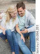 Купить «Hip young couple looking at smartphone sitting on skateboard», фото № 30084351, снято 19 февраля 2014 г. (c) Wavebreak Media / Фотобанк Лори