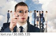 Купить «Composite image of businessman looking through magnifying glass», фото № 30085135, снято 11 июня 2014 г. (c) Wavebreak Media / Фотобанк Лори