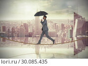 Купить «Composite image of businessman walking on tightrope and holding umbrella», фото № 30085435, снято 11 июня 2014 г. (c) Wavebreak Media / Фотобанк Лори