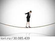 Купить «Composite image of businesswoman performing a balancing act on tightrope», фото № 30085439, снято 11 июня 2014 г. (c) Wavebreak Media / Фотобанк Лори