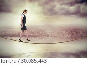 Composite image of redhead businesswoman stepping on tightrope. Стоковое фото, агентство Wavebreak Media / Фотобанк Лори