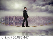 Купить «Composite image of handsome businessman stepping on tightrope», фото № 30085447, снято 11 июня 2014 г. (c) Wavebreak Media / Фотобанк Лори