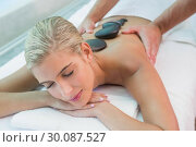 Купить «Beautiful woman receiving stone massage at health farm», фото № 30087527, снято 8 апреля 2014 г. (c) Wavebreak Media / Фотобанк Лори